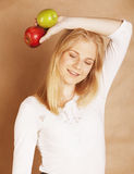 Young blond woman with green and red apple, good Royalty Free Stock Images