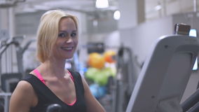 Young blond woman in a gym. Working out on the equipment looking down as she reads the digital monitor in a health and fitness concept stock video