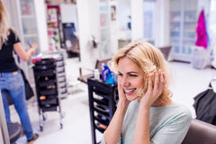 Young blond woman at hairdresser salon with new haircut Stock Photos