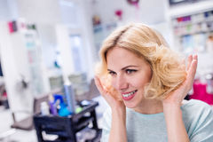 Young blond woman at hairdresser salon with new haircut Stock Images