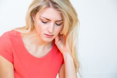 Young Blond Woman with Hand on Chin Looking Sad. Waist Up Portrait of Young Blond Woman with Long Hair and Hand Resting on Chin, Looking Down with Depressed or Stock Photos