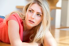 Young Blond Woman with Hand on Chin Looking Sad. Waist Up Portrait of Young Blond Woman with Long Hair and Hand Resting on Chin, Looking Down with Depressed or Stock Images