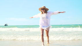 Young blond woman with hat and white tunic moves on thai beach stock footage