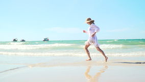 Young blond woman with hat and white tunic moves on thai beach stock video