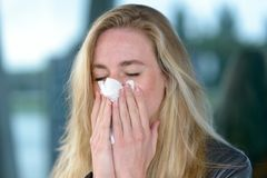 Young blond woman with hay fever. Portrait of young blond woman blowing her nose into tissue Stock Photography
