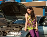Young blond woman with her broken car. Royalty Free Stock Images