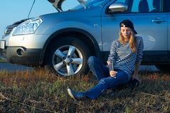 Young Blond Woman With Her Broken Car Stock Photo
