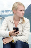 Young blond woman with her Smartphone in the hand Royalty Free Stock Photos