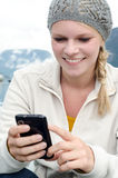 Young blond woman with her Smartphone in the hand Royalty Free Stock Photo