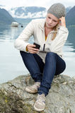 Young blond woman with her Smartphone in the hand Royalty Free Stock Photography