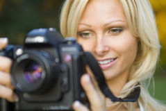 Young blond woman holding camera. Woman holding digital SLR camera Stock Photos