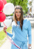 Young blond woman holding colorful balloons in the street. Royalty Free Stock Images