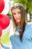 Young blond woman holding colorful balloons in the street. Royalty Free Stock Image