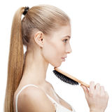 Young blond woman holding comb isolated on white Royalty Free Stock Photos