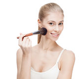Young blond woman holding cosmetics brush on white Stock Photo