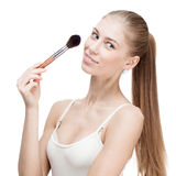 Young blond woman holding cosmetics brush on white Stock Image