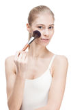 Young blond woman holding cosmetics brush on white Royalty Free Stock Photo