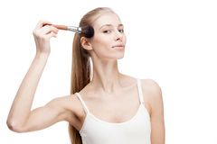 Young blond woman holding cosmetics brush on white Royalty Free Stock Photos