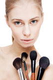 Young blond woman holding cosmetics brushes Royalty Free Stock Image