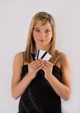 Young blond woman holding credit cards. Portrait of a beautiful young blonde woman in a black dress holding up credit cards on a white background stock images