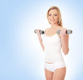 A young blond woman holding dumbbells Stock Photography
