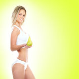 A young blond woman holding a fresh green pear Stock Photos