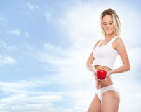 A young blond woman holding a fresh paprika Royalty Free Stock Photography