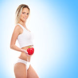 A young blond woman holding a fresh paprika Royalty Free Stock Images