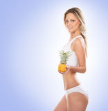 A young blond woman holding a fresh pineapple Royalty Free Stock Images