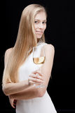 Young blond woman holding glass of white wine Stock Images