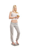 A young blond woman holding a hamburger Royalty Free Stock Image
