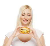 A young blond woman holding a hamburger Stock Image