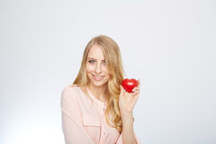 Young blond woman holding a red heart. isolated on Royalty Free Stock Photo