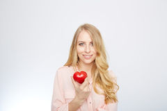 Young blond woman holding a red heart. isolated on Stock Photos