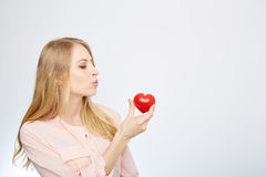 Young blond woman holding a red heart. isolated on Royalty Free Stock Photos