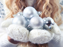 Young blond woman holding silver decorative balls wearing white Stock Photo