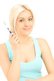 Young blond woman holding a tooth brush and looking at camera Stock Images