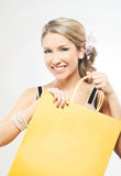A young blond woman holding a yellow shopping bag Royalty Free Stock Photo