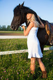 Young blond woman with horse. Young blond woman in white dress  with horse Royalty Free Stock Images
