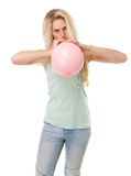 Young blond woman inflating balloon Royalty Free Stock Photo