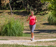Young blond woman jogging and listening to music in park Royalty Free Stock Photos