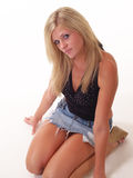 Young Blond woman kneeling in short skirt. Young blond woman in jeans skirt kneeling Royalty Free Stock Images