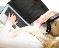 Young blond woman with laptop and headphones. Royalty Free Stock Image