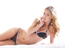 A young blond woman laying in black lingerie Royalty Free Stock Images
