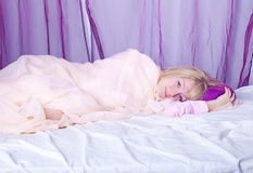 Young blond woman laying in her bed Stock Images