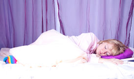 Young blond woman laying in her bed Royalty Free Stock Photos