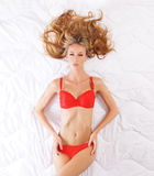 A young blond woman laying in red lingerie Stock Images