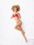 A young blond woman laying in red lingerie Stock Photography