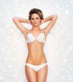 A young blond woman laying in white lingerie on snow Stock Photography