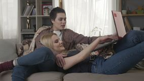 Young blond woman lies on the lap of a brunette and watching a funny video on laptop, laughing, friends, lesbians. Leisure, rest, humor 60 fps 4k stock video